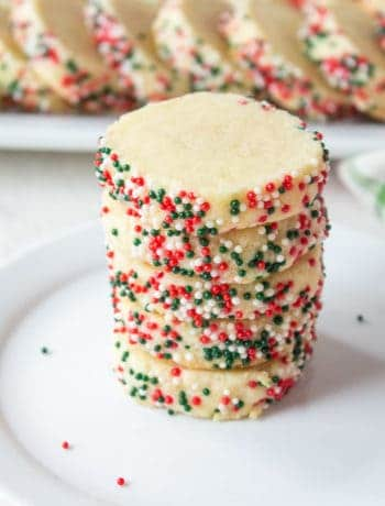 A stack of sugar cookies with red, green and white sprinkles on the edges.