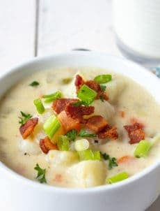 A bowl of creamy soup with potatoes and topped with bacon and green onions.