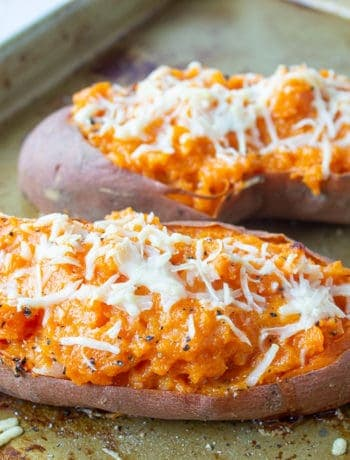 Twice baked sweet potatoes topped with shredded parmesan cheese on a baking sheet.