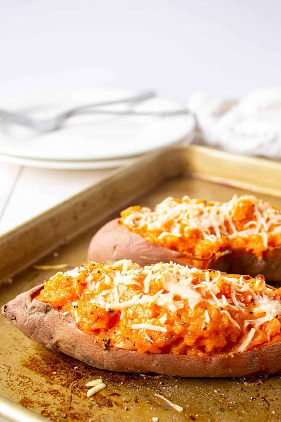 Sweet potatoes topped with cheese on a baking sheet.