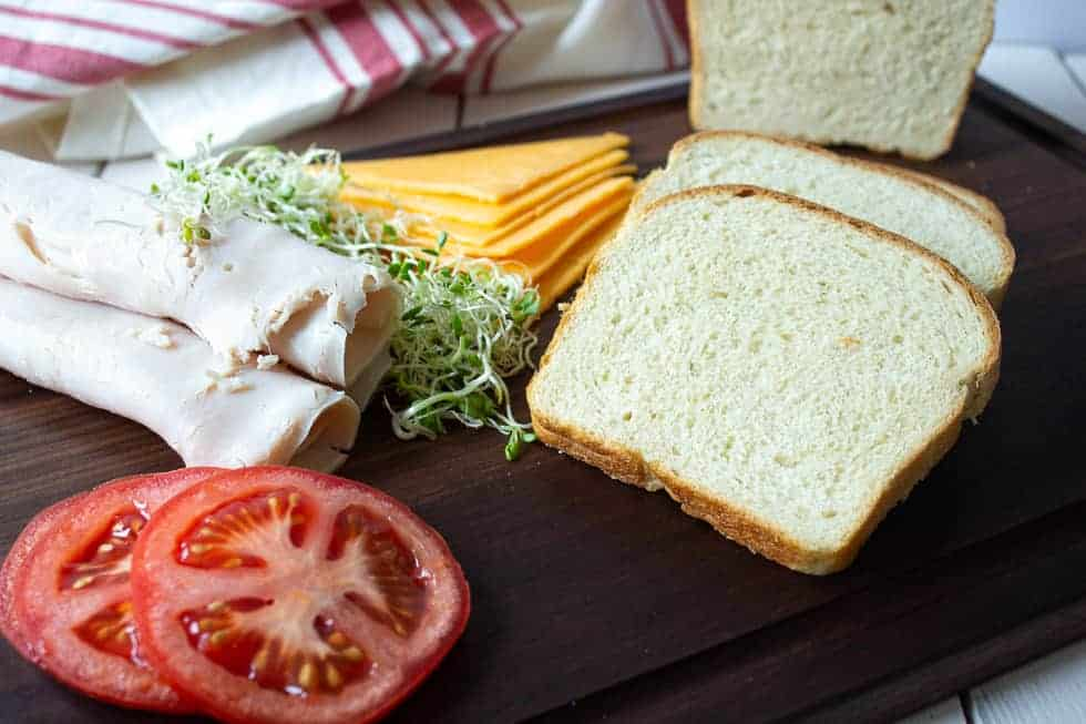A wooden board topped with sliced bread, tomatoes, turkey, cheese and sprouts.