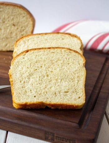 Sliced white bread on a walnut cutting board.