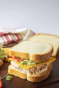 Turkey sandwich with tomatoes, cheese and sprouts on a brown board.
