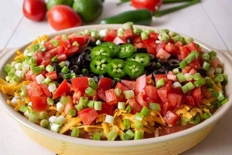 Mexican dip topped with fresh tomatoes and cheese in a yellow casserole dish.
