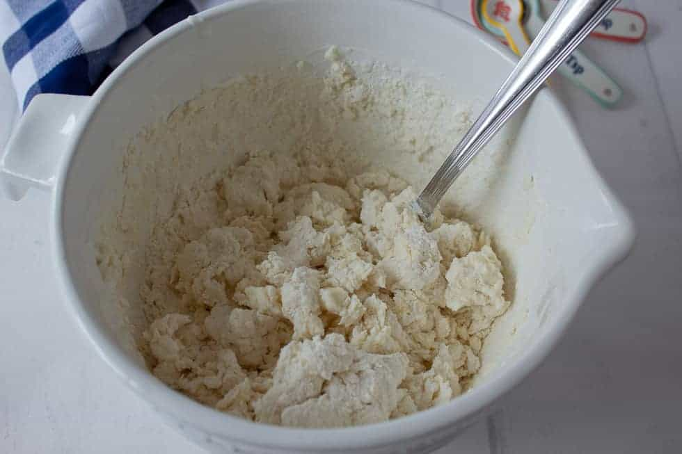 Biscuit dough in a white bowl.