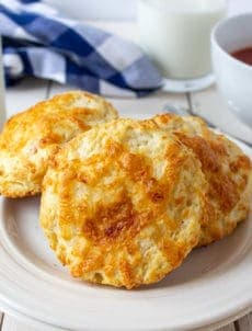 A plate filled with three cheesy biscuits.