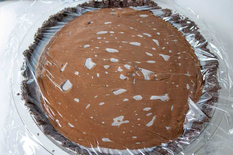 Plastic wrap on top of a chocolate pie.