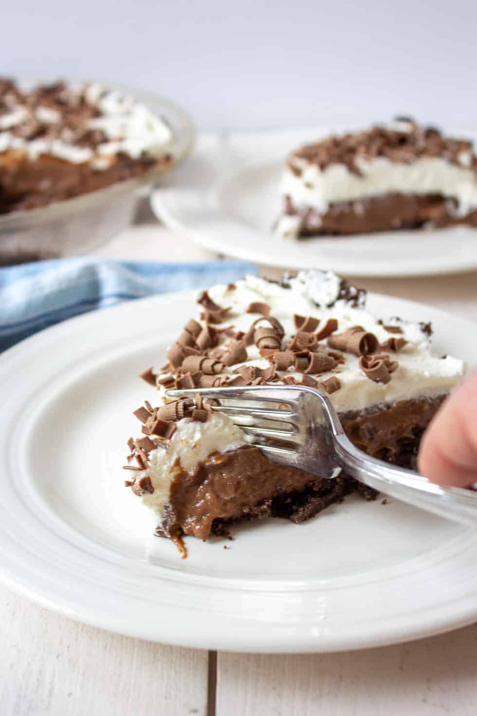 A fork slicing into a piece of chocolate pie topped with whipped cream.