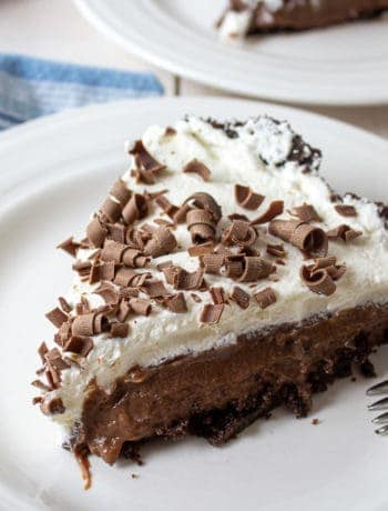 A slice of chocolate cream pie topped with whipped cream and chocolate shavings.