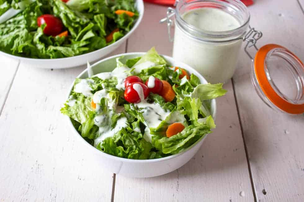 Green salad with tomatoes, onions and a creamy salad dressing.