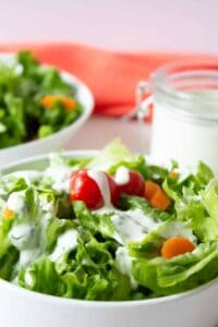 A green salad topped with a creamy white dressing.