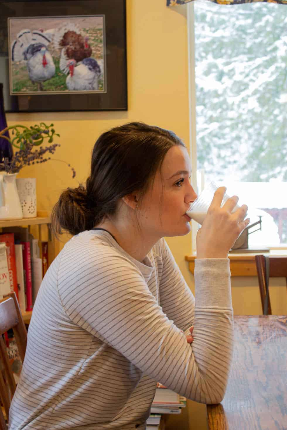 A girl drinking a glass of milk at a kitchen table.