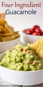 A white bowl with guacamole and a chip stuck in the guacamole.