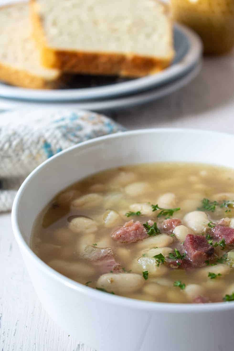 A bowl of soup with white beans and ham.