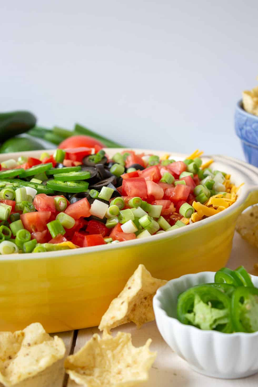 Chips scattered on a board in front of a yellow casserole dish filled with a layered dip.