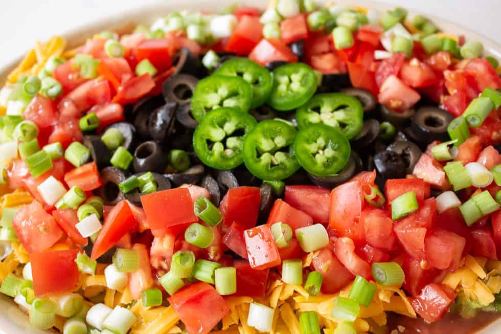 Chopped tomatoes, green onions, olives and jalapenos on top of a dip.