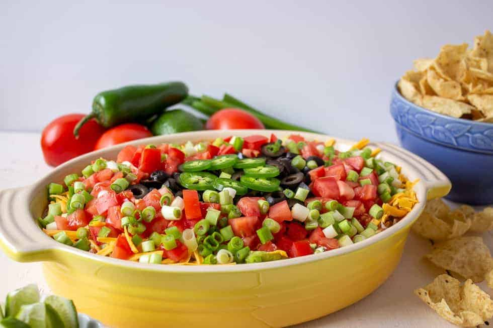A colorful dip topped with fresh tomatoes, green onions and olives.