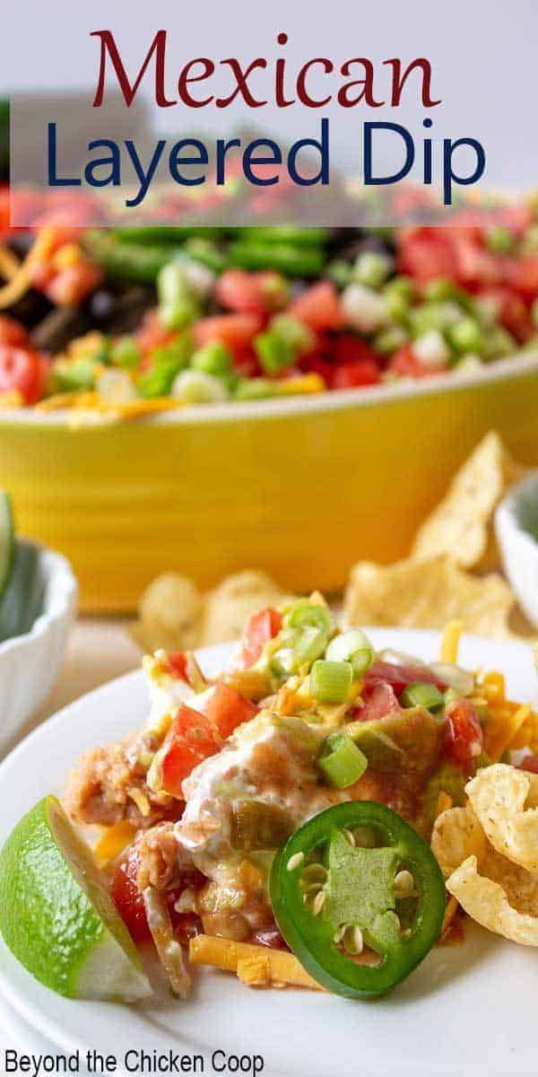 7 layer dip on a plate with fresh limes and tortilla chips.