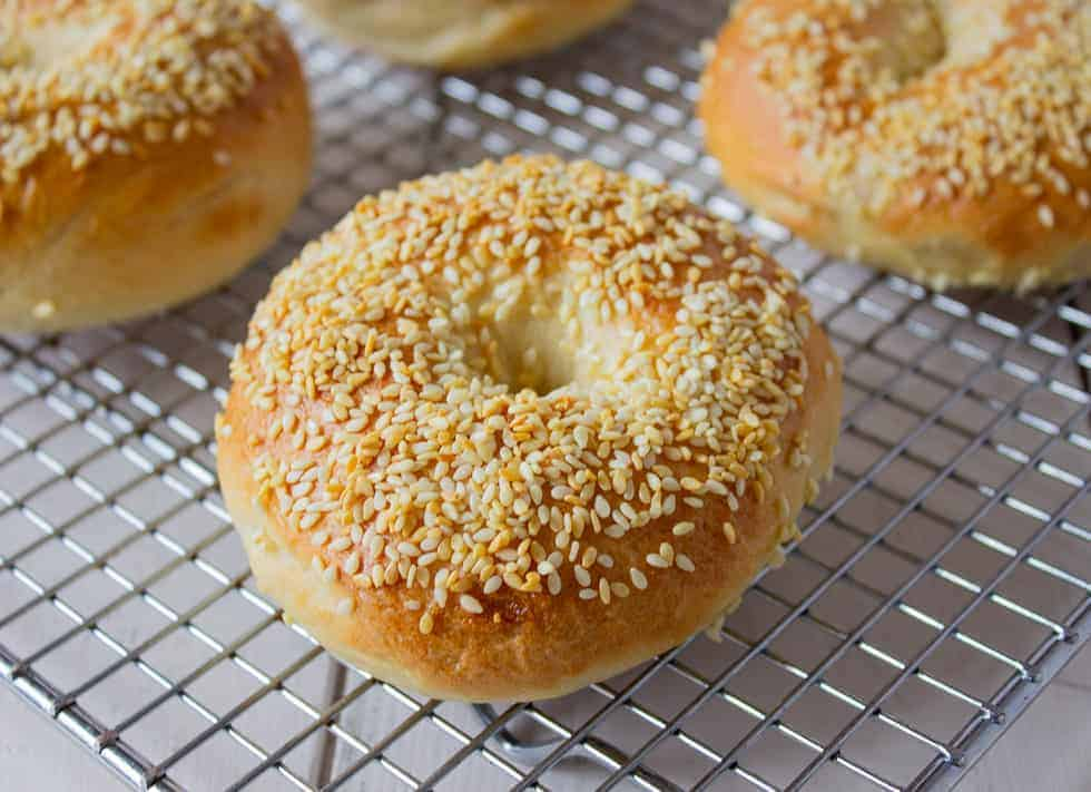 Sesame seed bagel on a baking rack.