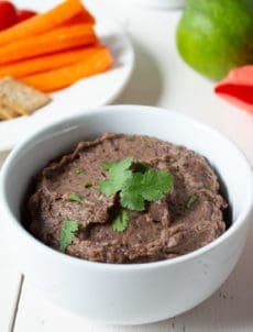 A white bowl filled with a dark bean dip topped with fresh cilantro.