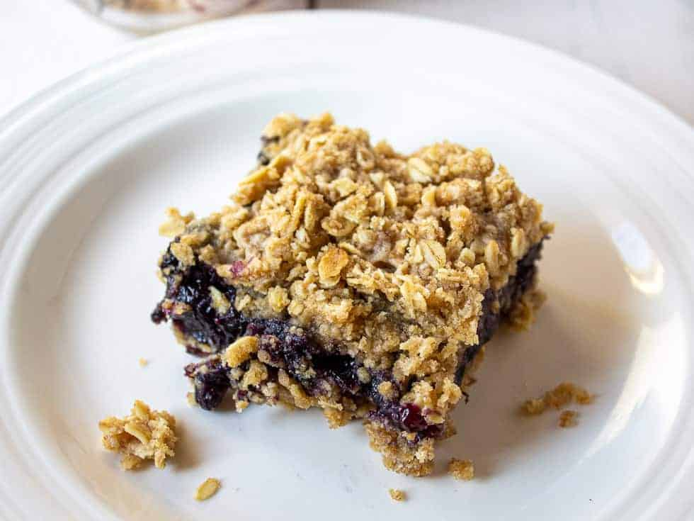 Oatmeal bars with a blueberry filling cut into a square piece.