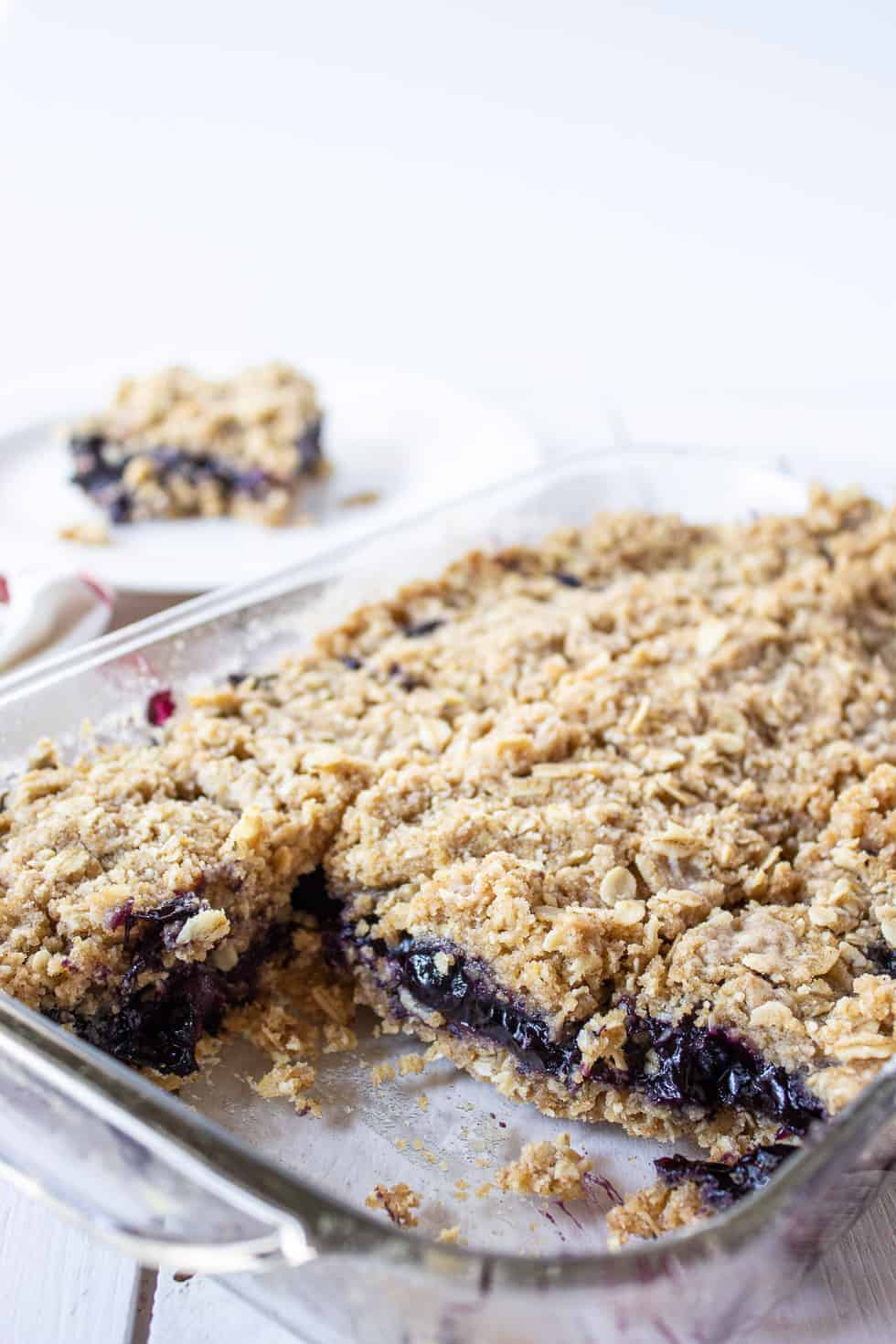 A glass dish filled with blueberry crumb bars.