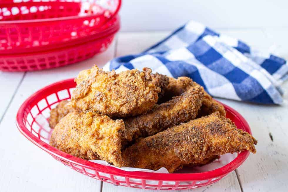 A red basket filled with fried chicken strips.