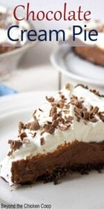 A slice of chocolate pie topped with whipped cream and topped with chocolate shavings.