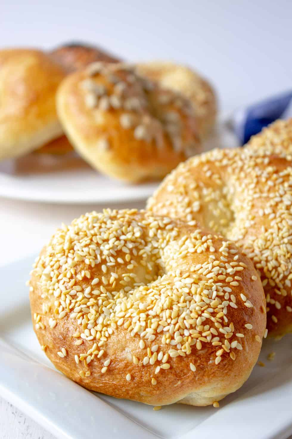 Sesame bagels lined in a row on a white platter.