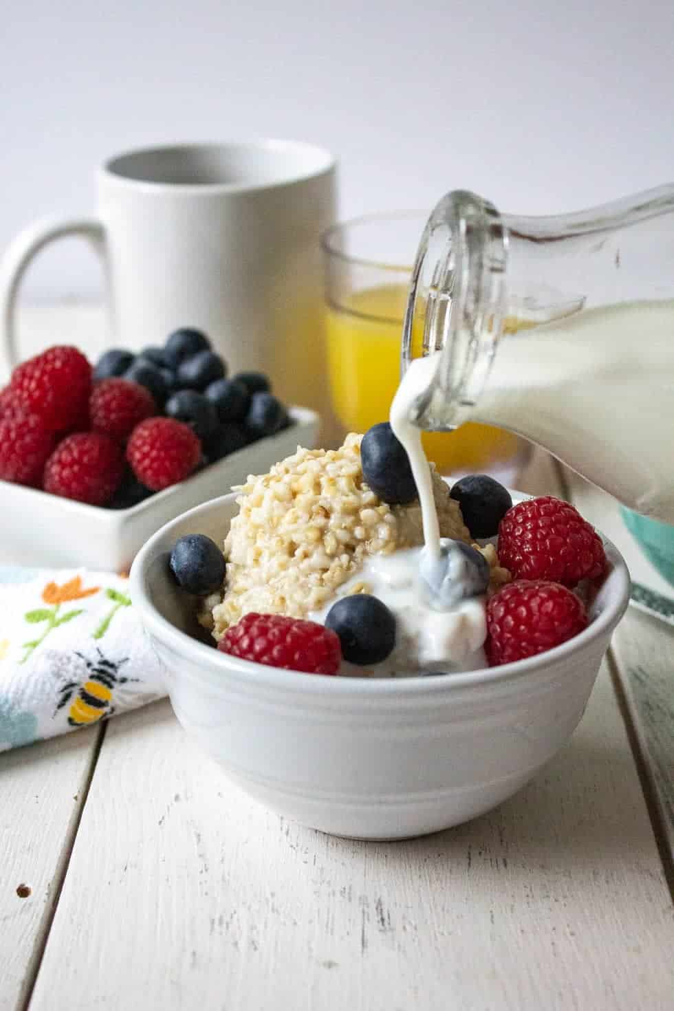 Milk being poured over a bowl full of oatmeal and fruit.