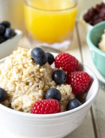 A bowl filled with a hot cereal and topped with fresh blueberries and raspberries.