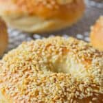 Sesame seed topped bagels on a baking rack.