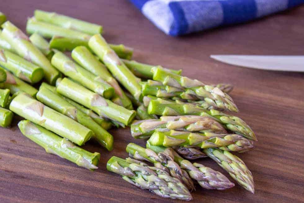 Chopped asparagus on a wooden cutting board.