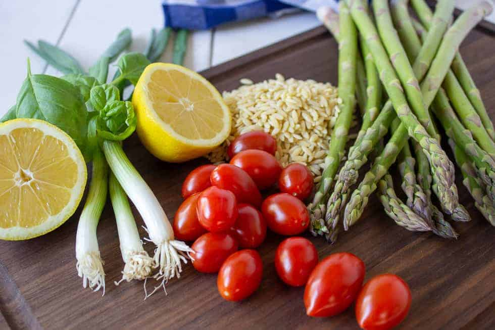 A board topped with asparagus, tomatoes, orzo, green onions and a half of a lemon.