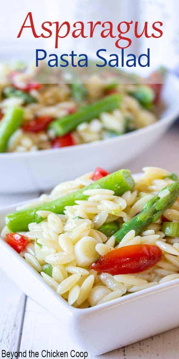 Orzo pasta with asparagus and tomatoes in a small bowl.