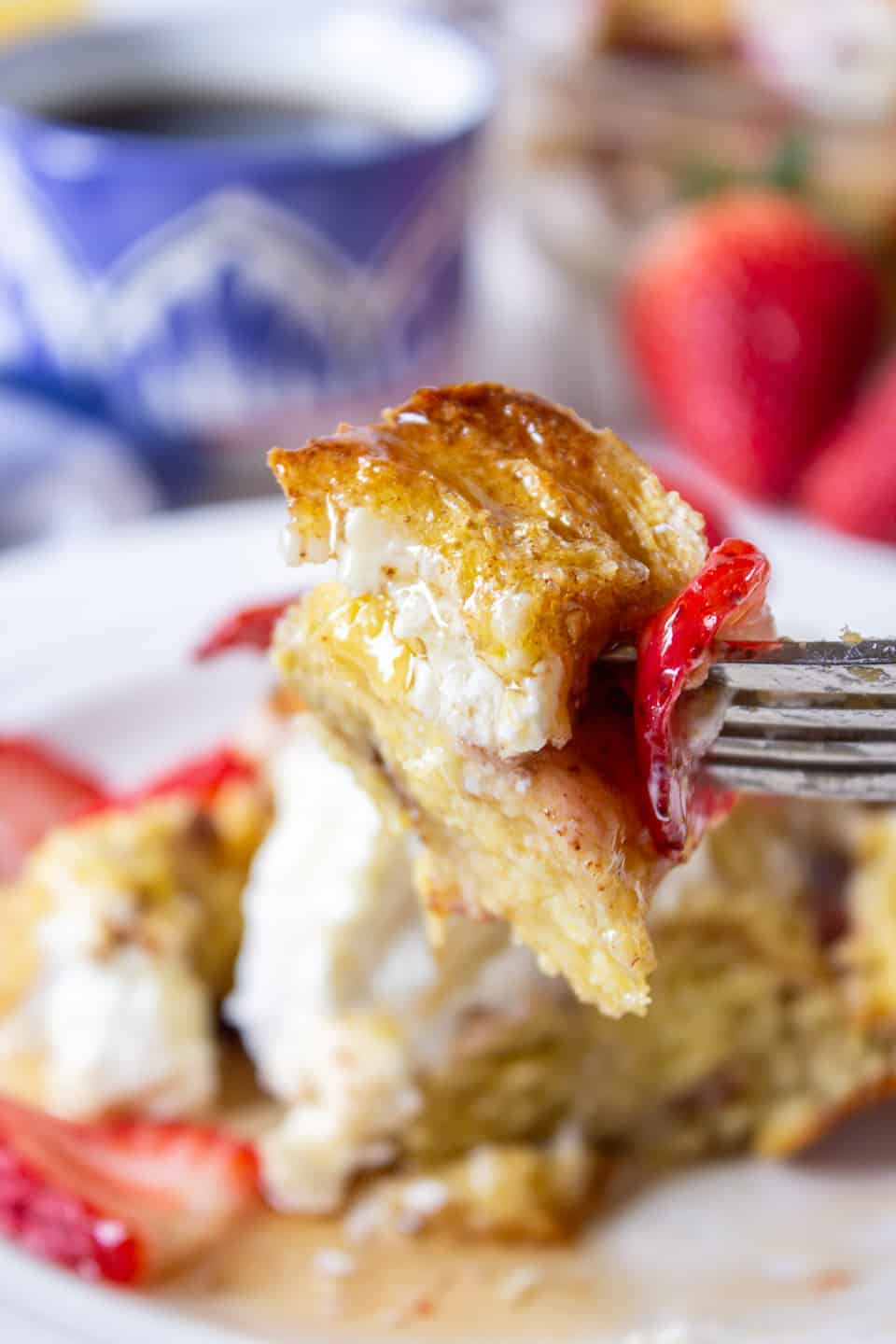 A forkful of baked french toast with strawberries.