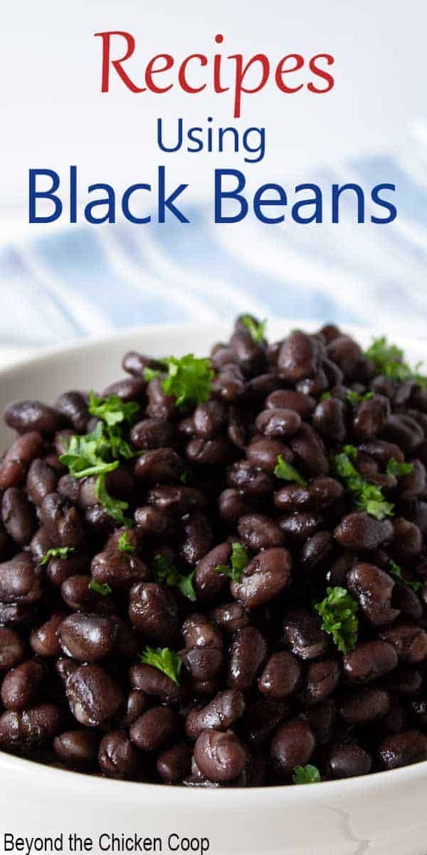 A large bowl filled with cooked black beans topped with a fresh green herb.