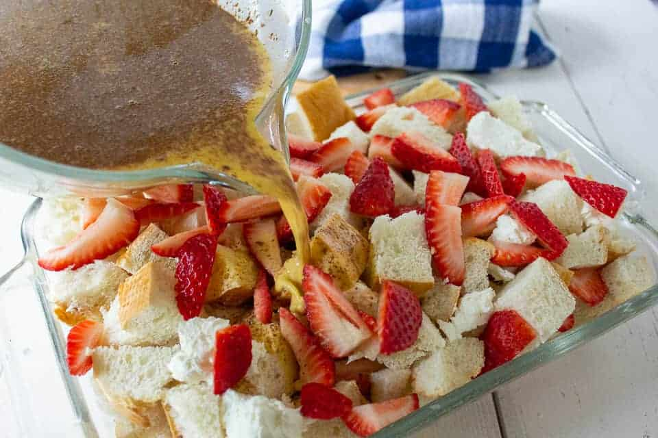 Egg mixture being poured over a casserole dish filled with bread and strawberries.