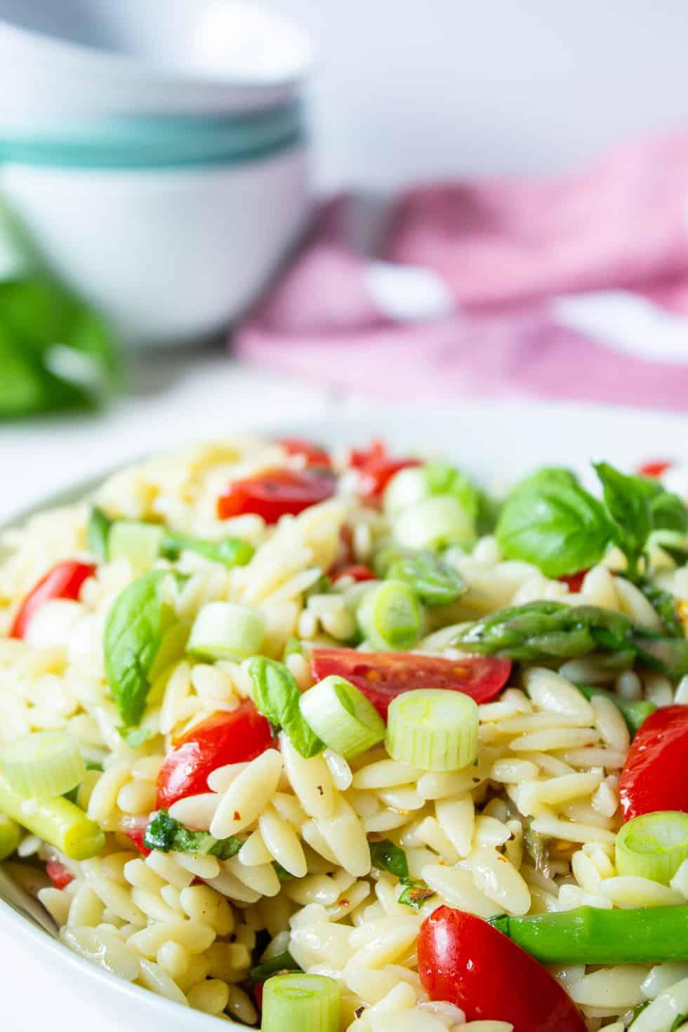 Asparagus, tomatoes and pasta in a bowl.