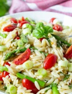 Pasta salad with chopped asparagus and tomatoes.