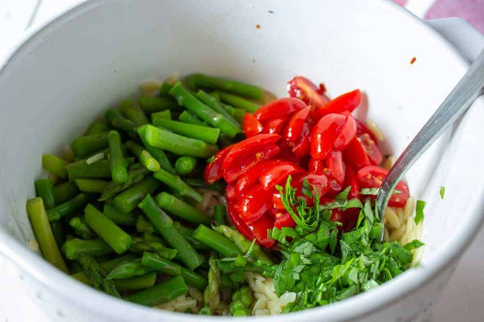 Fresh chopped tomatoes along with asparagus in a bowl.