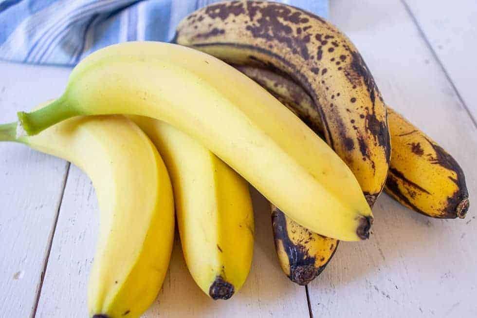 Yellow bananas next to overripe bananas.