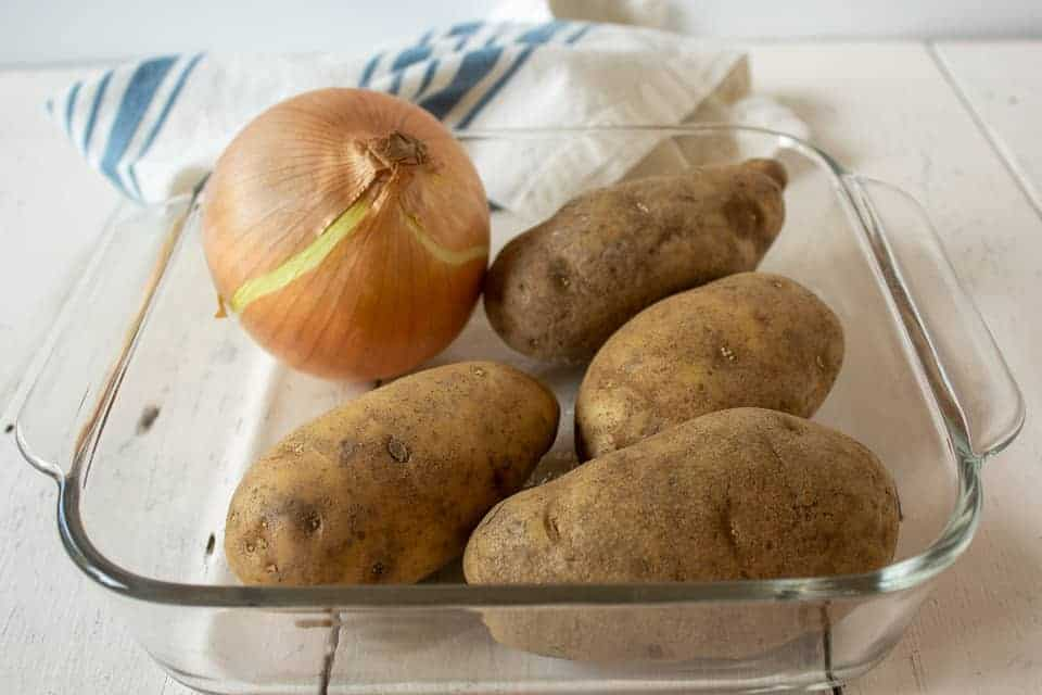 Potatoes and an onion sitting in a glass casserole dish.