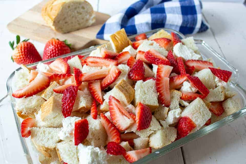 Cut strawberries and cubes of cream cheese layered in a breakfast casserole.