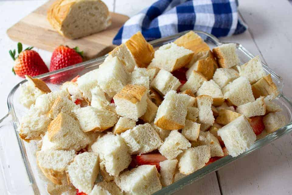 Layers of bread cubes and strawberries in a glass casserole dish.