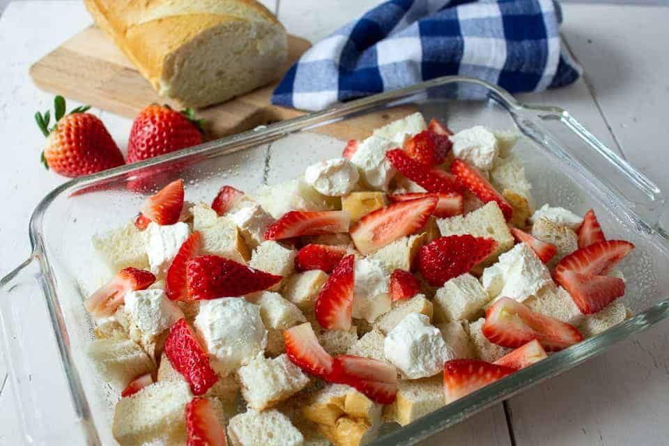 A glass baking dish filled with bread, strawberries and cream cheese.