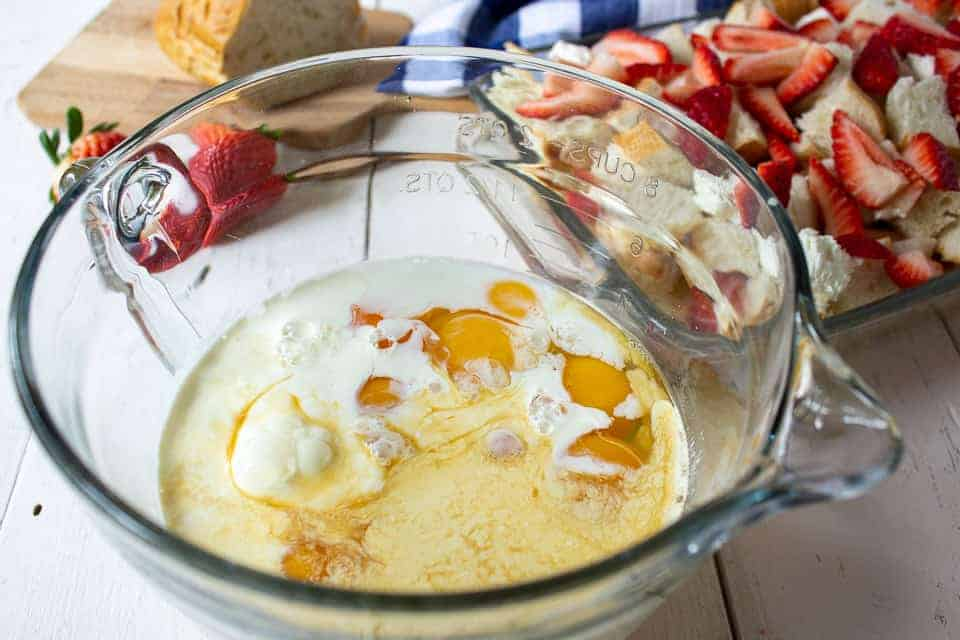 Eggs and milk in a large glass bowl.