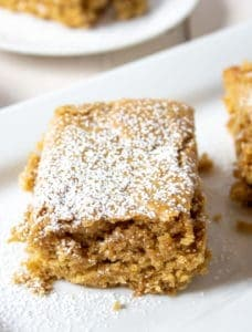 Square pieces of spice cake topped with powdered sugar.