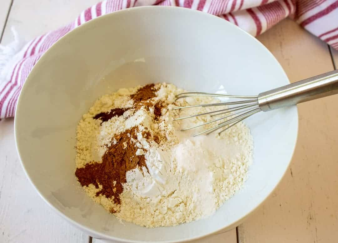 Flour and spices in a bowl with a small whisk.