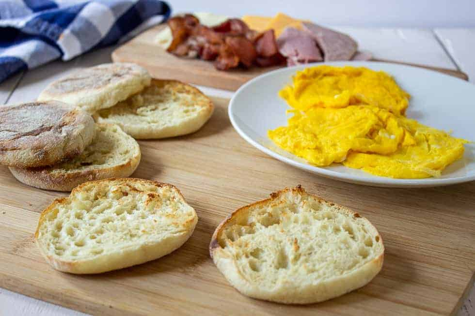 A toasted English muffin on a wooden board with a plate of eggs behind it.